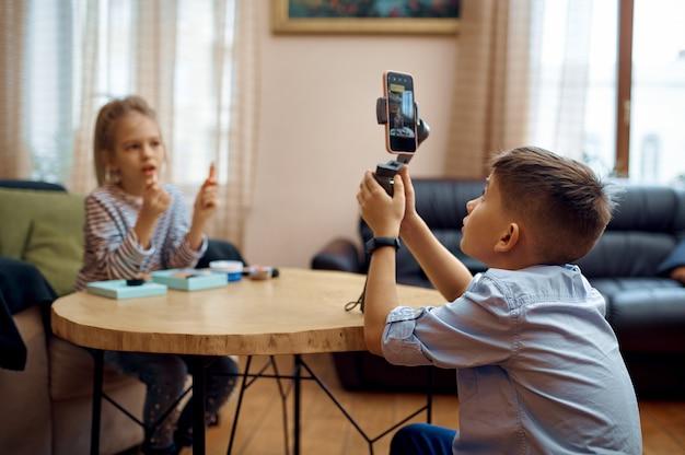 Twee kinderbloggers nemen blog op camera op, kleine vloggers