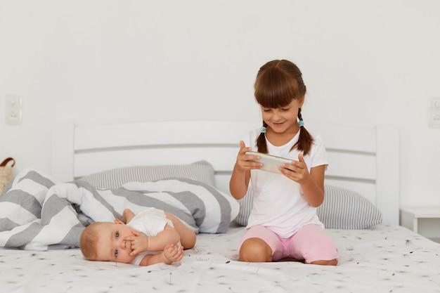 Twee kinderen broers en zussen poseren op bed in lichte kamer, ouder meisje kijken tekenfilms op smartphone binnen, baby baby kinderen liggen in de buurt van charmant meisje met staartjes.