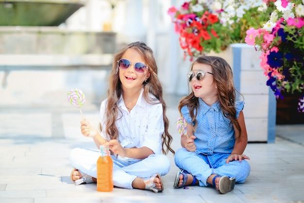 Twee kinderen die snoep eten, loly-pop op straat