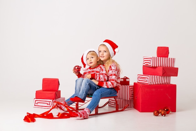 Twee kinderen een jongen en een meisje in truien en hoeden santa zitten op een slee om geschenken te dragen. studio, witte achtergrond, ruimte voor tekst