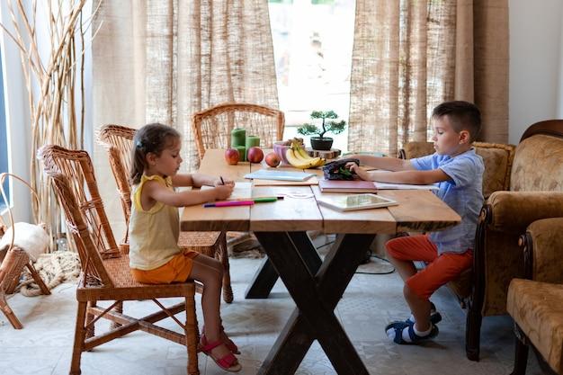 Twee kinderen, een jongen en een meisje, maken hun huiswerk, zittend aan een grote houten tafel in de eetkamer van hun huis, ze tekenen en schrijven, ze ontwikkelen hun creativiteit.