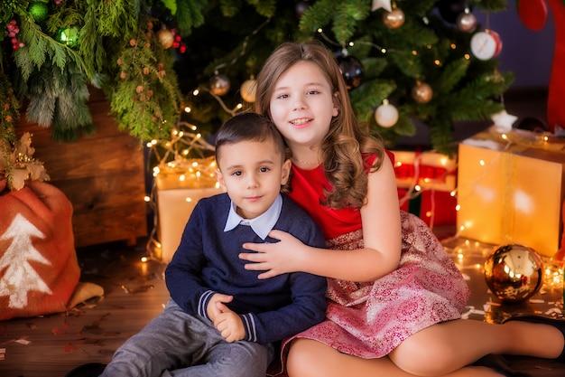 Twee kinderen een meisje en een jongen in de buurt van een kerstboom