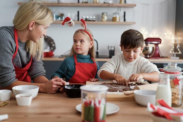 Twee kinderen en hun moeder die peperkoekkoekjes uitsnijden