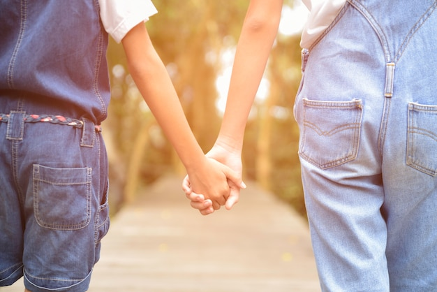 Twee kinderen hand in hand elkaar op de houten weg