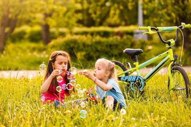 Twee kinderen in het park blazen van zeepbellen en plezier maken