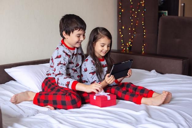 Twee kinderen in rode en grijze pyjama's zitten thuis op het bed