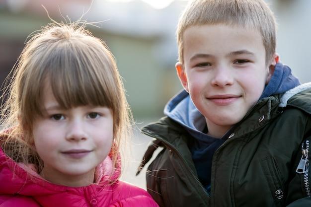 Twee kinderen jongen en meisje gek rond plezier samen buitenshuis op zonnige herfstdag. gelukkig jeugdconcept.