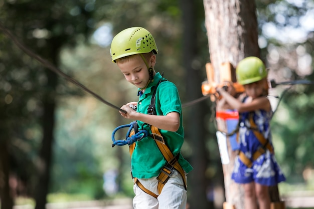 Twee kinderen, jongen en meisje in beschermende uitrusting en veiligheidshelmen bij het beklimmen van activiteit op touwmanier.