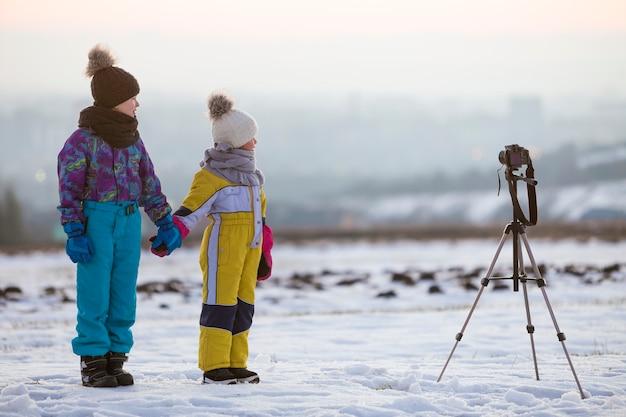 Twee kinderen jongen en meisje plezier buiten in de winter spelen met fotocamera op een statief op besneeuwd veld.
