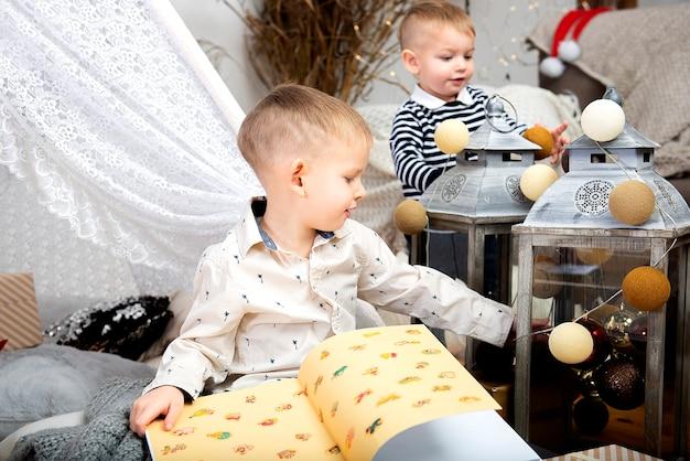 Twee kinderen kinderen jongens spelen tussen kerst geschenkdozen in een versierd huis. prettige kerstdagen en fijne feestdagen!