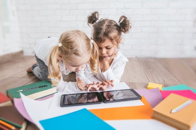 Twee kinderen, kleine meisjes van voorschoolse leeftijd kijken naar tablet thuis op de vloer
