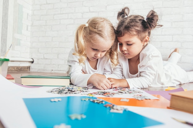Twee kinderen, kleine meisjes van voorschoolse leeftijd, legden de puzzel in elkaar op de vloer