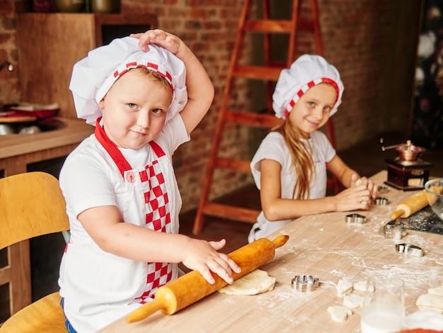 Twee kinderen koken in een binnenlandse keuken. gelukkig gezin, gelukkige kinderen concept