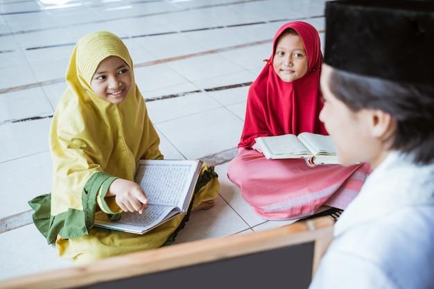 Twee kinderen leren koran lezen en wijzen naar een zwart bord met moslimleraar of ustad in moskee