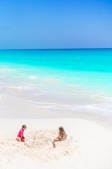 Twee kinderen maken zandkasteel en plezier op tropisch strand