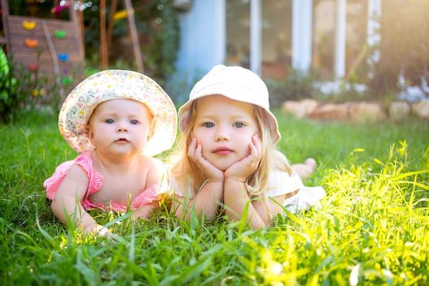 Twee kinderen meisjes zussen op een groen gazon in de zomer in de zon in hoeden
