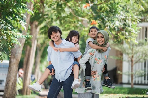 Twee kinderen met hun ouders piggybackride