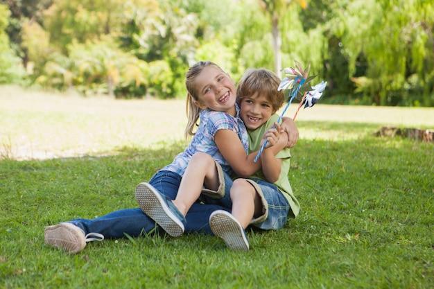 Twee kinderen met pinwheels spelen in het park