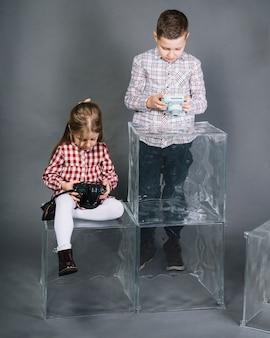 Twee kinderen met transparante blokken die camera tegen grijze achtergrond bekijken