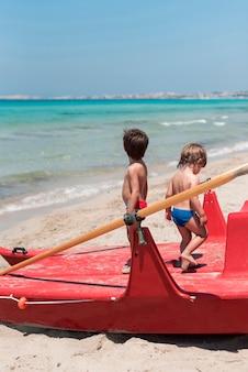 Twee kinderen op het strand staan op peddel boot