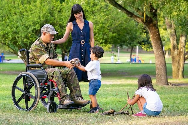Twee kinderen regelen hout voor kampvuur buiten in de buurt van moeder en gehandicapte militaire vader in rolstoel. jongen die logboek toont aan vader. gehandicapte veteraan of familie buitenshuis concept