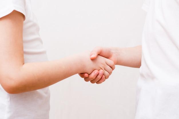 Twee kinderen schudden elkaar de hand als ze elkaar ontmoeten