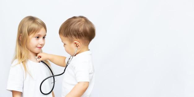 Twee kinderen spelen dokter geïsoleerd op wit