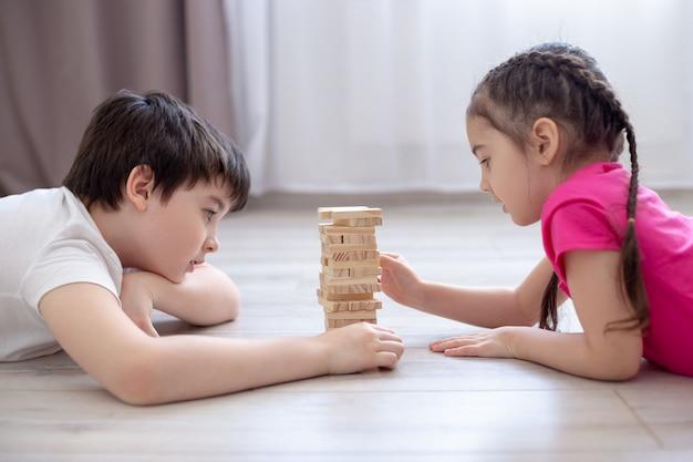 Twee kinderen spelen een spelletje jenga op de vloer
