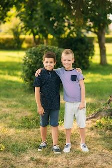 Twee kinderen spelen in het park. twee mooie jongens in t-shirts en korte broeken hebben plezier met glimlachen. ze eten ijs, springen, rennen. de zomer is zonnig.