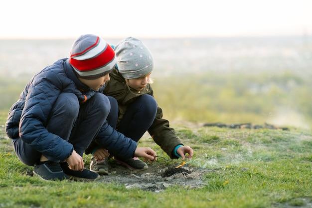 Twee kinderen spelen met vuur buiten bij koud weer.