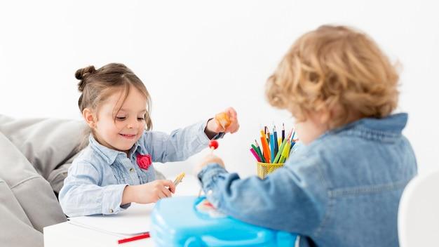 Twee kinderen spelen samen aan balie