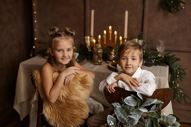 Twee kinderen zitten op stoelen bij een feesttafel
