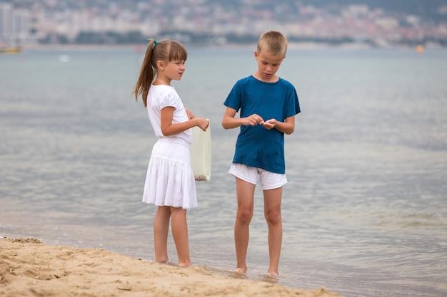 Twee kinderenjongen en meisje die blootvoets op overzees kustwater lopen in de zomer.