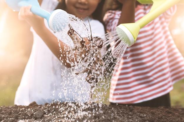 Twee kinderenmeisje die droge boom met het water geven van pot samen in uitstekende kleurentoon water geven