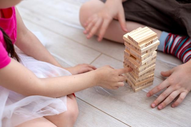 Twee kinderhanden verzamelen een toren van houten blokken op de vloer. detailopname. gezinsbordspellen