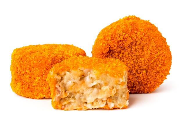 Twee kipnuggets en de helft op een wit, close-up.