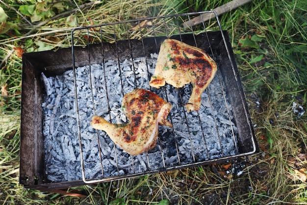 Twee kippenpoten worden gebakken op de grill