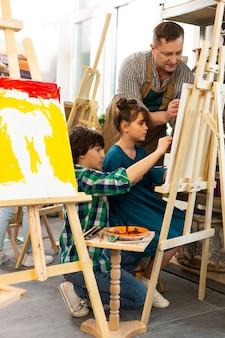 Twee klasgenoten die bij de kunstles schilderen die zich dichtbij tekenezel bevinden