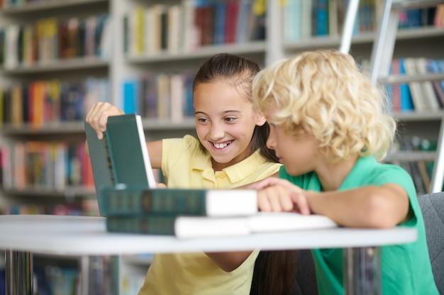 Twee klasgenoten die hun huiswerk maken aan de bibliotheekbalie