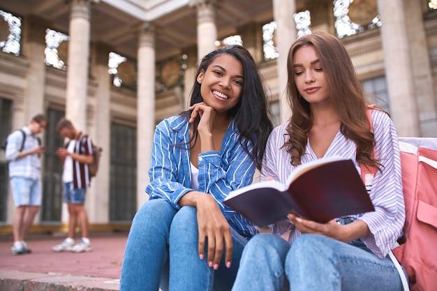 Twee klasgenoten op straat bij een grote pauze midden op de dag wachtend op het begin van de lessen