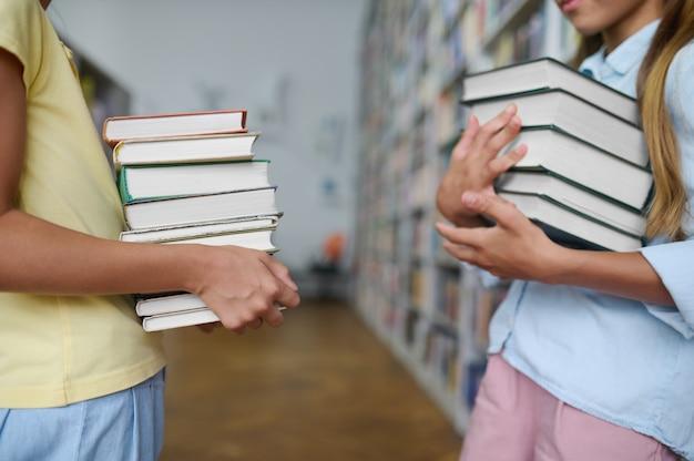 Twee klasgenoten staan tussen boekenkasten in een openbare bibliotheek