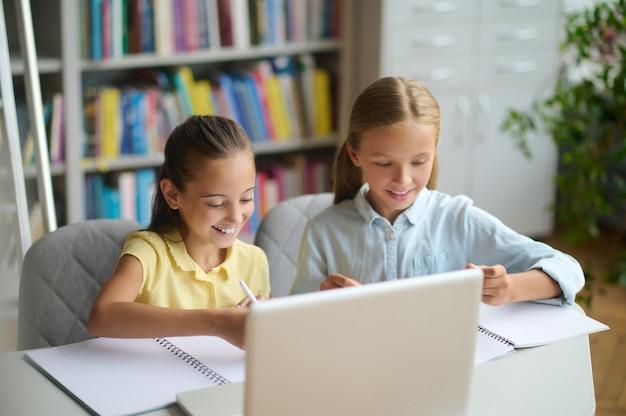 Twee klasgenoten studeren aan een openbare bibliotheek