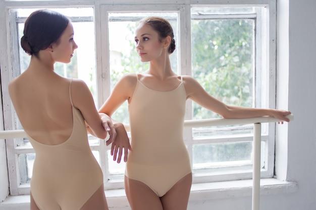 Twee klassieke balletdansers poseren op barre