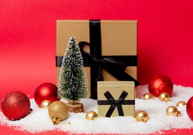 Twee klassieke kerstdozen met kerstballen en sneeuw eromheen