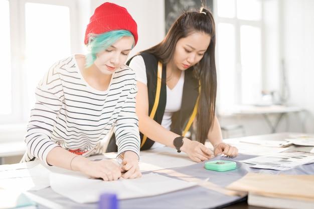 Twee kleermakers naaien in atelier workshop