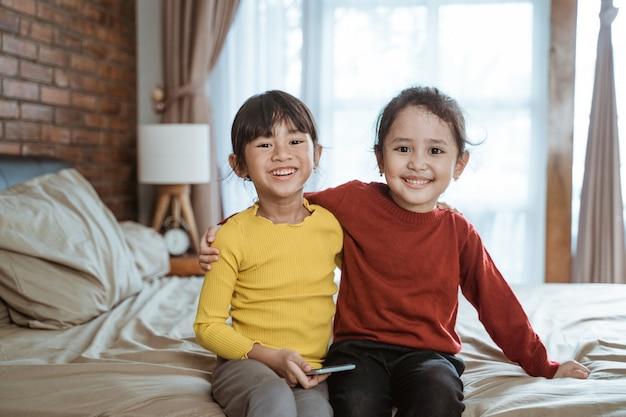 Twee kleine aziatische meisjes lachen gelukkig kijken naar de camera