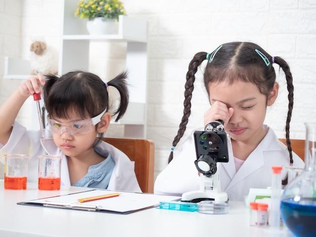 Twee kleine aziatische sibling meisjesrol die een wetenschapper in wetenschapslaboratorium spelen met materiaal. leren en onderwijs van kind.