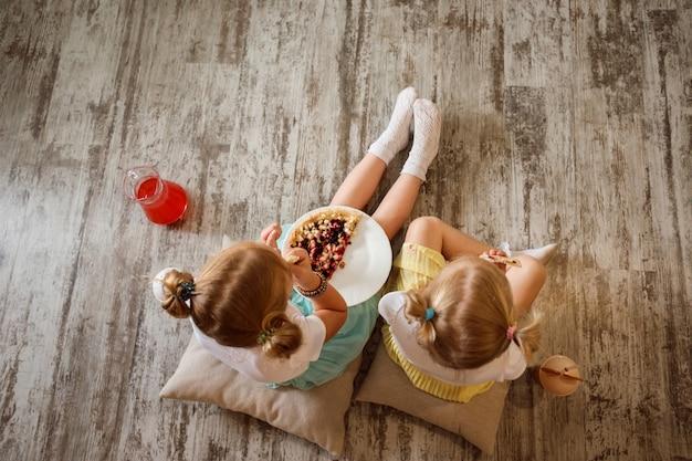 Twee kleine blonde meisjes, zussen zitten op de grond op kussens, eten pizza en drinken sap. thuis samen tijd doorbrengen.