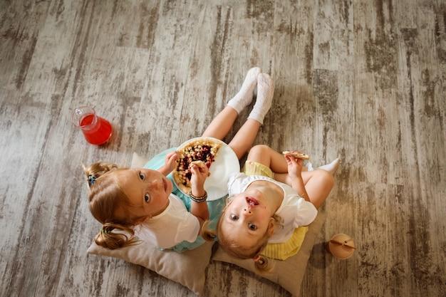 Twee kleine blonde meisjes, zussen zitten op de grond op kussens, eten pizza en drinken sap