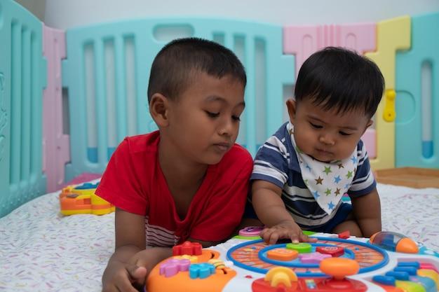 Twee kleine broer baby spelen speelgoed in de kamer